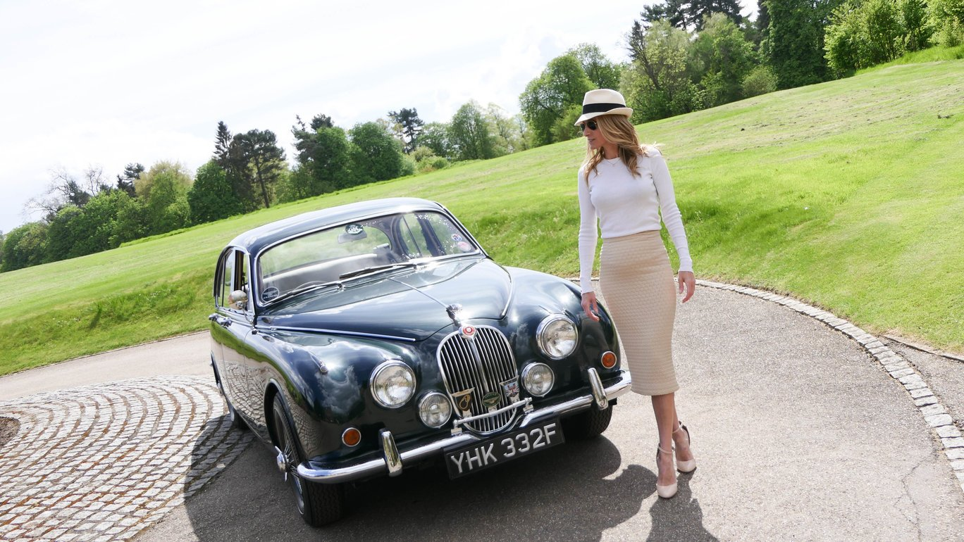 jaguar classic car. woman professional driver standing next to the car. luxury lifestyle